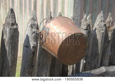 A bucket hanging on a wooden picket fence in Fort Michilimackinac, Michigan