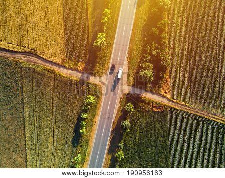 Aerial view of traffic on two lane road through countryside and cultivated fields