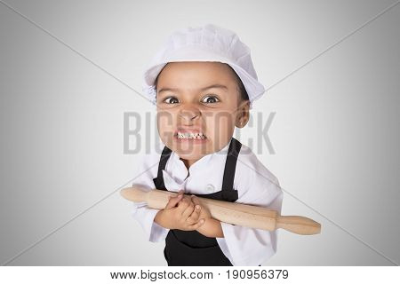 Portrait of a funny and angry four years girl on grey background wit a roller on the hands