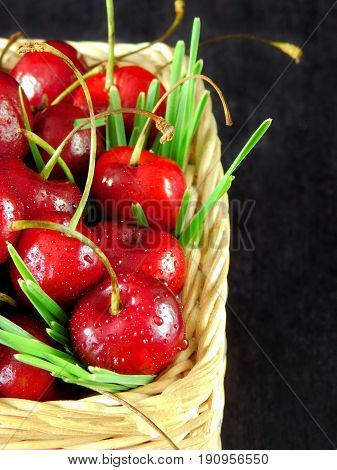 Close-up of cherries with drops in a wicker basket