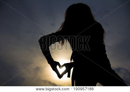 Silhouette of a young hipster woman body shape posture with hands form symbol in heart shape on sunset sky and cloud on the mountain.