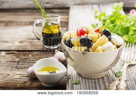 Cold summer pasta salad, black olives, mozzarella, juicy tomatoes and mint leaves in a ceramic marble bowl on a simple wooden background with herbs and olive oil to serve. Selective focus.