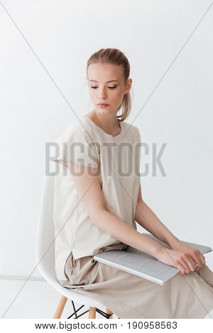 Image of concentrated blonde lady sitting indoors. Looking aside reading book.
