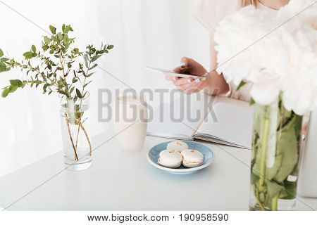 Cropped image of young woman sitting indoors make photo of sweeties with mobile phone.