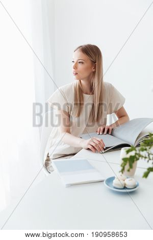 Photo of young woman sitting indoors reading book. Looking aside.