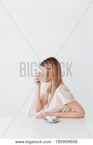 Image of young lady sitting isolated near sweeties covering face with coffee.