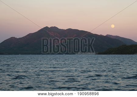 The moon rising behind the mountain during the sunset