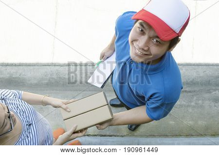 delivery man toothy smiling face and woman accepting delivering goods box at home