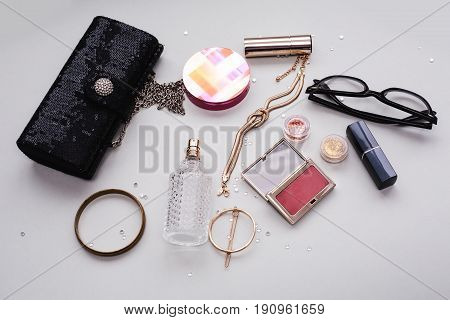 Makeup cosmetics products and accessories on grey background