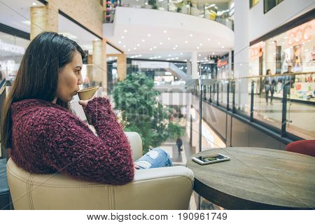 young woman drink coffe in coffe cup in mall cafe