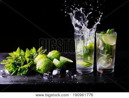 Refreshing summer cocktail mojito lemonade with splashes. Party cocktail. Lime, ice and mint on the table. Black background. Close-up. Copy space for text.