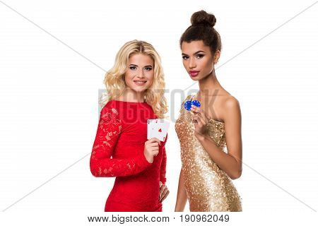 Beautiful african woman and Caucasian young woman with long light blonde hair in evening outfit. Holding playing cards and chips. Isolated on white background. Poker