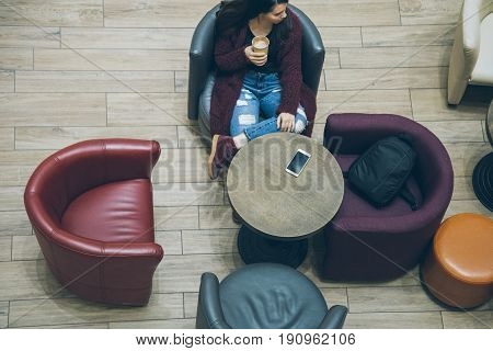 young woman drink coffe in coffe cup in mall cafe top view