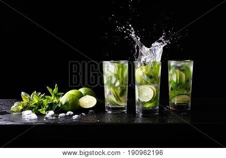 Mojito summer beach refreshing tropical cocktail non alcohol drink in highball glass with splash soda water, lime juice, mint leaves, sugar, ice and rum. Dark black background with copy space text