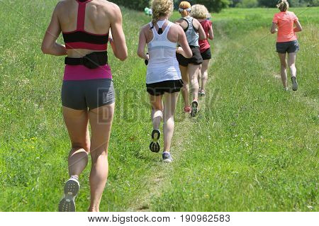 Outdoor cross-country running group of young active people running in nature