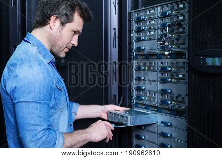Server room. Nice professional male technician holding a blade server and installing it in the server rack while doing his job