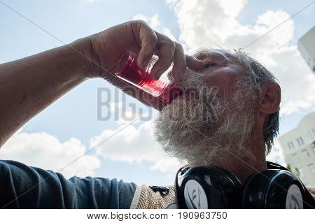 Orel Russia June 12 2017: Russia protests. Dritry Krayukhin human rights activist drinking red compote symbol of corruction close up