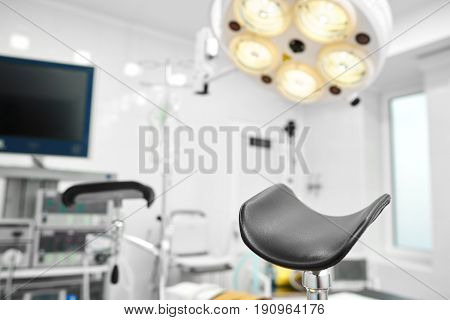 Selective focus on a part of gynecological chair in an operating theatre at the hospital with surgical lamp in the background. Copyspace. Healthcare medicine gynecology concept.