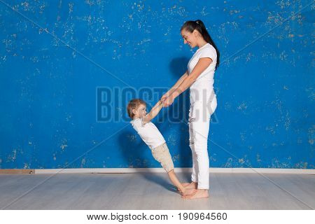 mom playing with young son in a room with blue walls