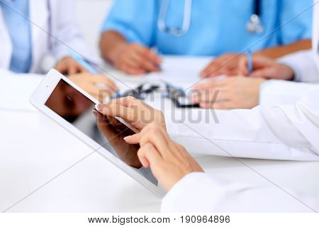 Group of doctors at medical meeting. Close up of physician using tablet computer