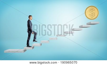 A businessman on blue background walking up a concrete block stairs where a giant golden coin stands on the top. Roadway to wealth. Get rich. Monetary motivation.