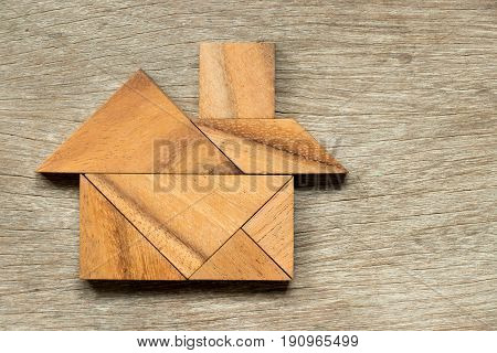 Wooden tangram puzzle in home shape background