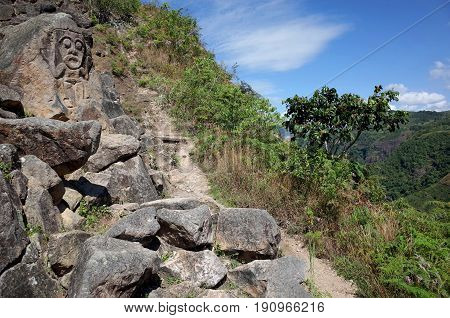 An ancient rock carving looks out over the valley near San Agustin archaeological park Colombia