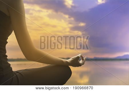 Close-up of feminine and masculine arms and crossed legs during meditation on river with sky background.