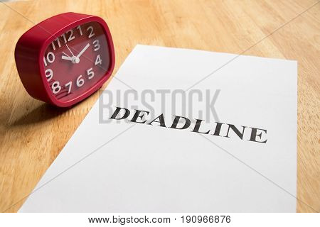 Red analog clock and paper with deadline word on wooden table background