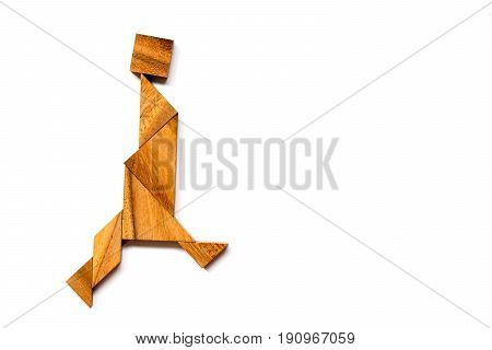 Wooden tangram puzzle in walking man shape on white background