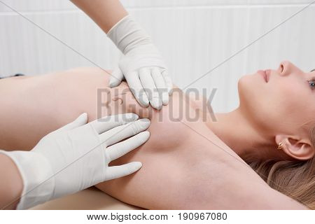 Cropped shot of a female doctor drawing lines on the breast of her female patient preparing for breast augmentation plastic surgery medicine concept.