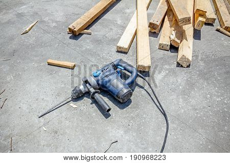 Handy electric drill is lying down on clean concrete background.
