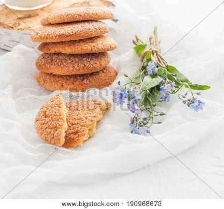 On A White Table, Sandy Round Cookies, One Broken And A Bouquet Of Blue Forget-me-not Flowers, A Top