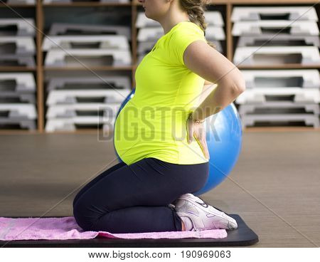 Woman at prenatal yoga class in the gym.