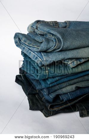 Stack of jeans fashion background different denim layers colors