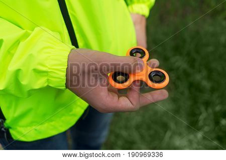 trendy fidget spinner - someone holding orange fidget spinner in hand, close up view