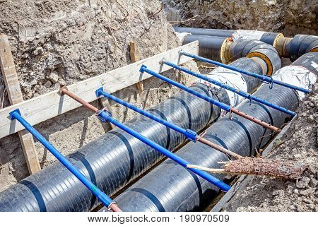 Trench walls are reinforced with supports to prevent sloughing of the soil.