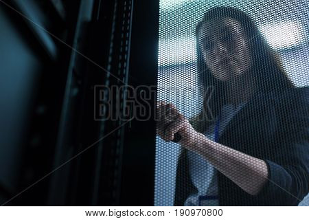 Door to the communication server. Pleasant beautiful nice woman holding the handle and opening the door while checking the data center equipment
