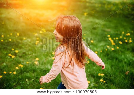 Little girl running along the green lawn with yellow dandelions, back view. Background image, concept on the theme of happiness, childhood and carefree.