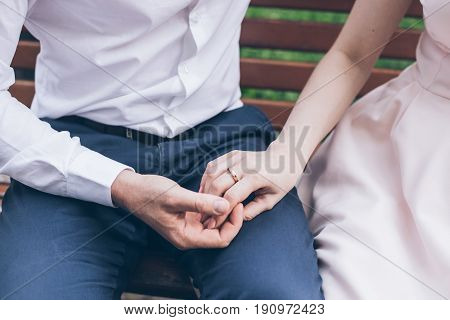 close up man hold woman hand while sitting on the bench