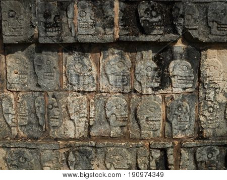Stone carvings of skulls of sacrificed Mayan ball court players, Chichen Itza, Mexico.