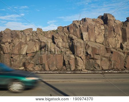 Basalt rock at side of roadway with motorist.