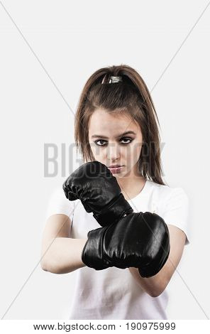 Boxing concept. Boxer woman making direct hit for defense isolated on gray looking at camera.