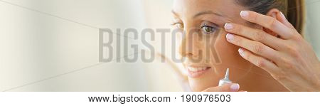 Beautiful young woman applying eye concealer on, template