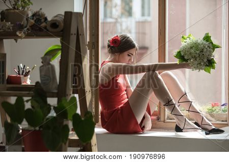 Young Girl In Red Dress In Orangery With Flower