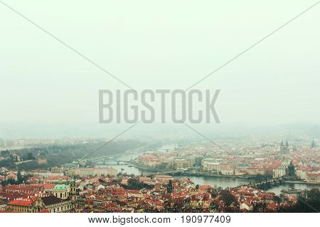 Aerial view of Prague skyline - old town, Charles bridge, Vltava river and red roofs on a foggy winter day. Generous space for copy.