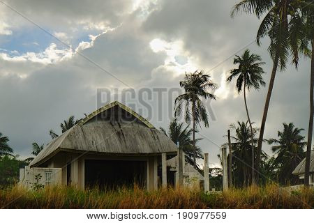 Tropical bungalow and old house with palms trees on stormy sunset cloudy sky background, Maenam beach, Koh Samui, Thailand
