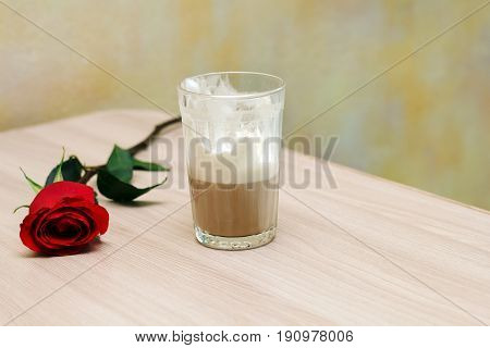 unfinished coffee and rose on table in coffee shop