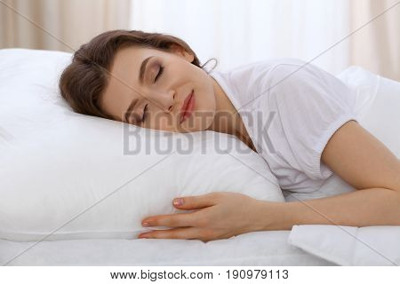 Beautiful young woman sleeping while lying in bed comfortably and blissfully. Early morning, you wake up for work or the day off concept.