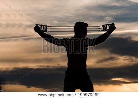 Silhouette Of Man With Muscular Body Workout With Expander Gripper